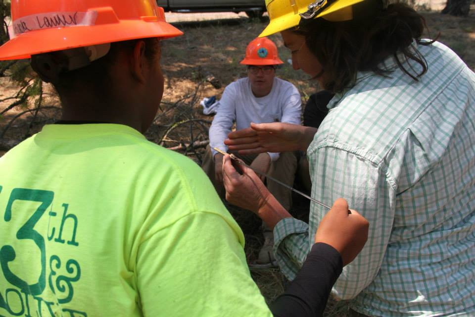 Lyndia Hammer, Lomakatsi Restoration Ecologist, is shown here demonstrating how to read tree cores in her discussion of forest ecology with youth participants.