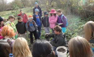 Lomakatsi staff member Ryan Puckett instructs students on proper tree planting technique.